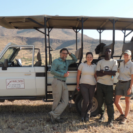 A rhino ranger is being a guide for some tourists, they are standing outside their vehicle in the desert landscape