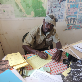A rhino ranger is sitting at his desk making a report