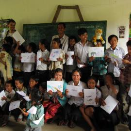 School children hold up their drawings of forest wildlife as part of the awareness raising campaign.