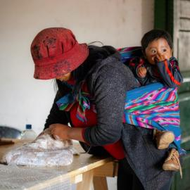 Argentinean artisan at work with her baby on her shoulders. Credit: Nilce Silvina Enrietti