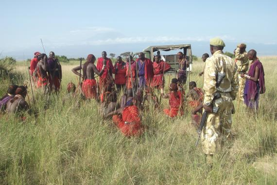 Members of the Maasai communities are employed as community scouts and are gathered around.